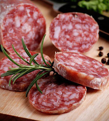 Sliced hard salami on cutting board with sprig of rosemary